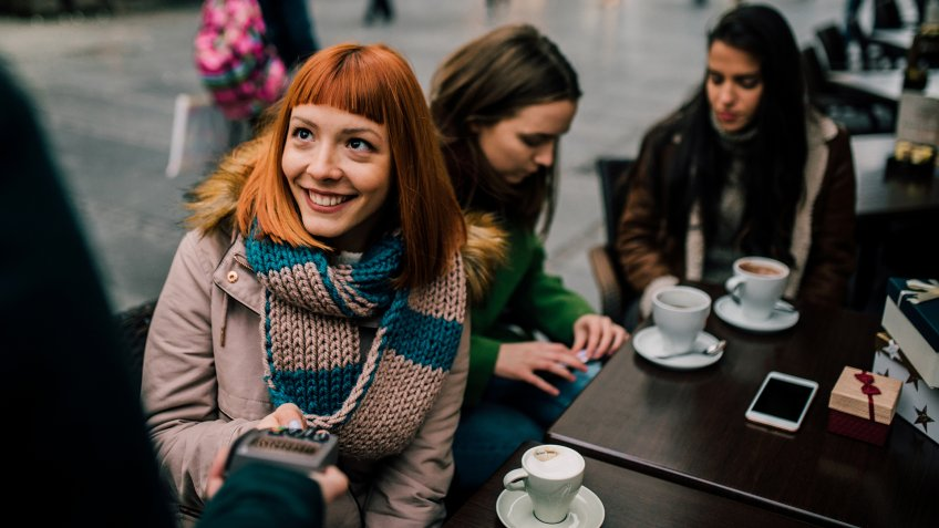 Happy young girl with red hair paying with credit card at coffee shop.