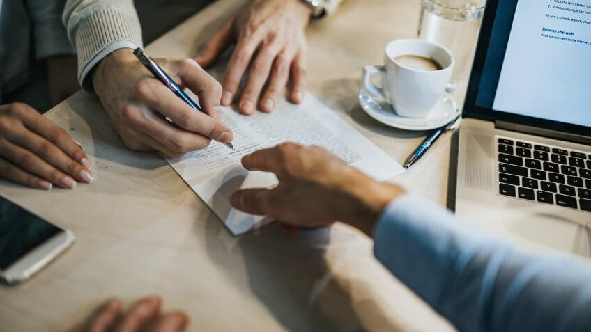 Unrecognizable man signing a contract while financial advisor is aiming at the place he need to sign.