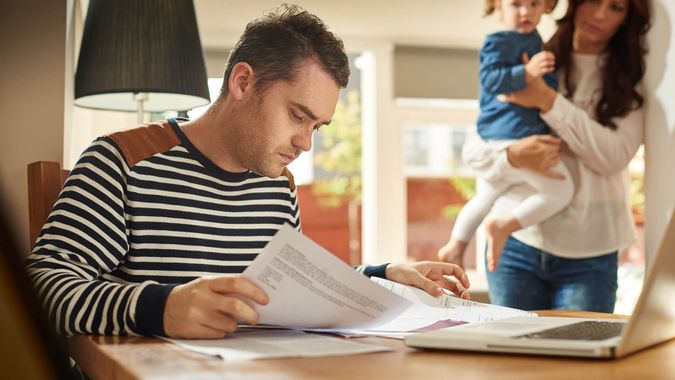 A young husband and father sits at a dining table looking through the household bills and looks worried .