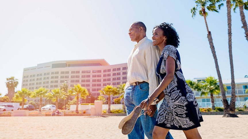 African mature couple in love walking on the beach.