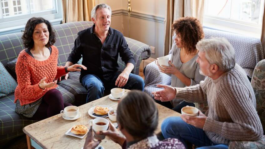 Group Of Middle Aged Friends Meeting Around Table In Coffee Shop.