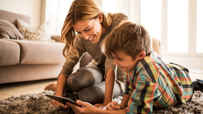 Mother and son are looking at digital tablet on the floor.