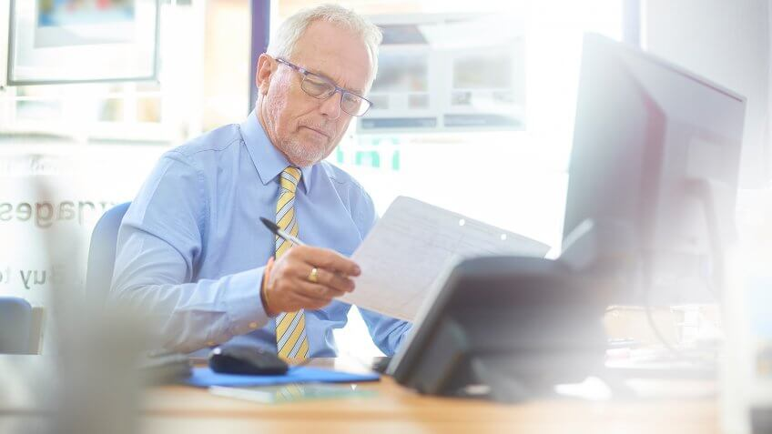 Mature businessman in office environment working at his desk.