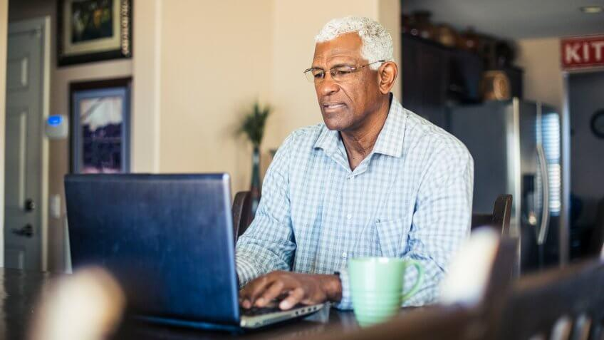 A senior black man works from his computer at home.