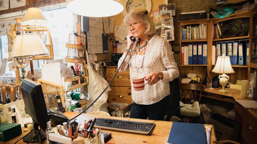 Senior woman working, talking on the phone.