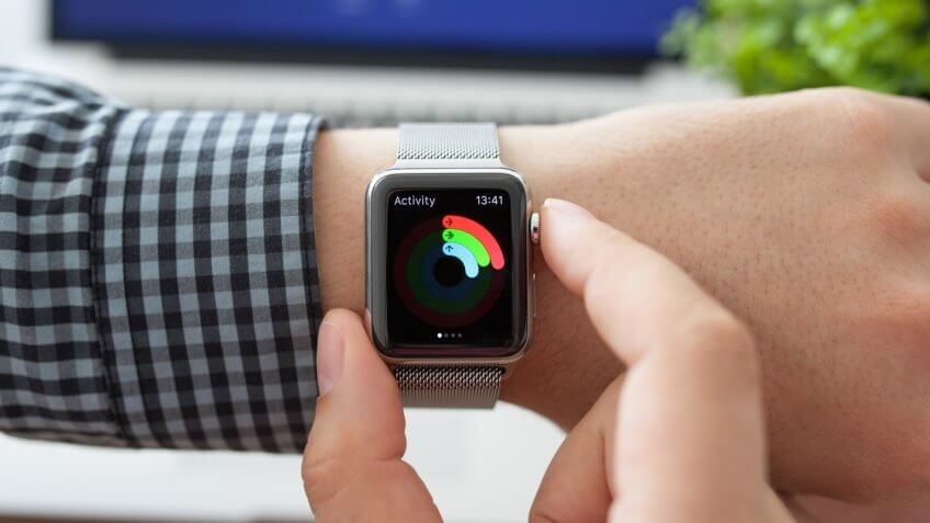 Alushta, Russia - August 11, 2015: Man hand with Apple Watch with app Activity on the screen and Macbook.
