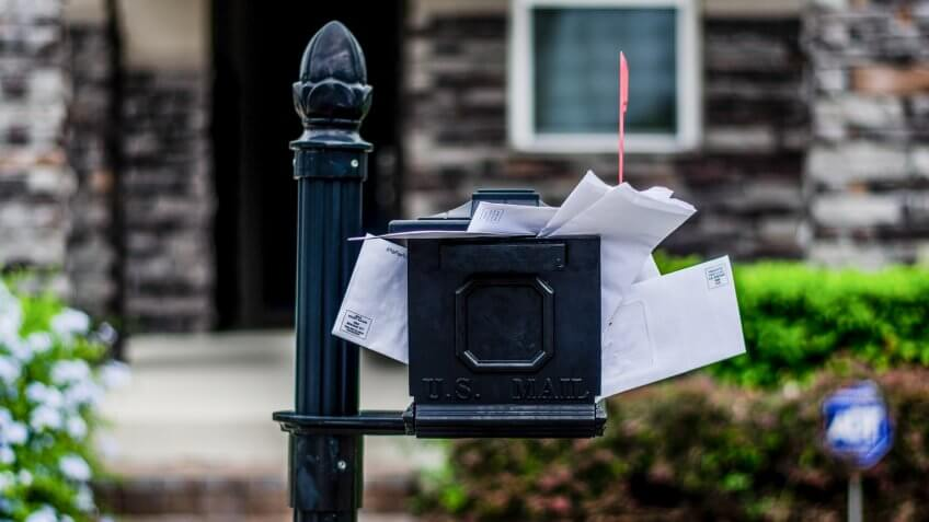 Mailbox with bills overflowing.