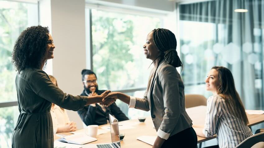Shot of two young businesswomen shaking hands after a successful business meeting in the office at work during the day.