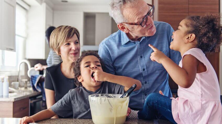 Grandparents making cupcake with kids.