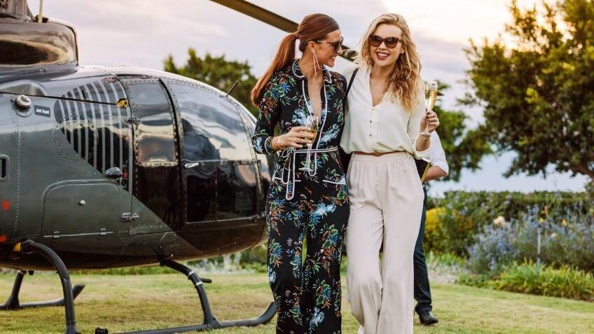 Two young women walking away from a helicopter with a glass of wine in their hands.