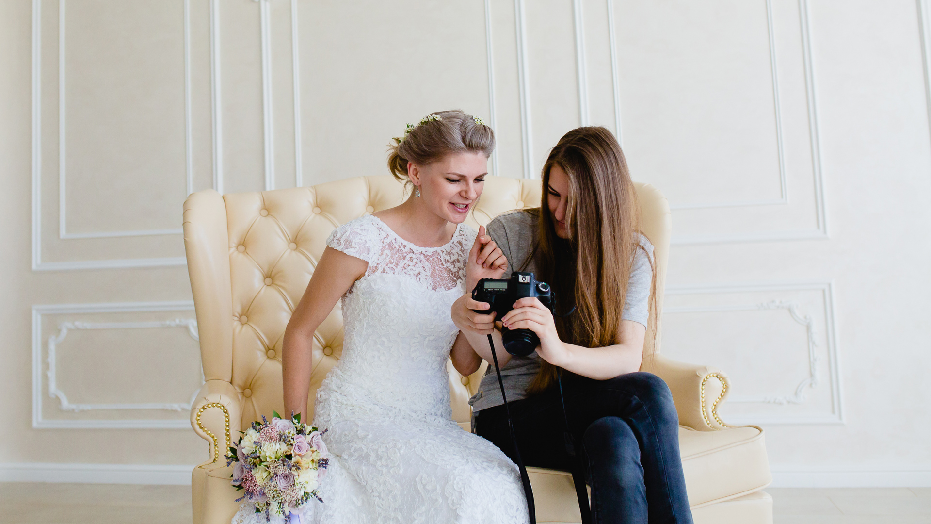 Photographer with long hair shows the young sexy bride had just taken photos.