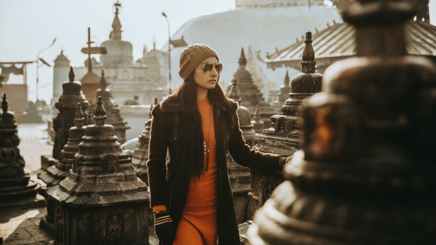 Beautiful young women standing at Nepal temple  in winter wear.
