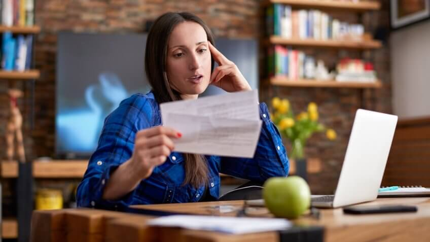 Woman is holding overdue bills before making online payment.