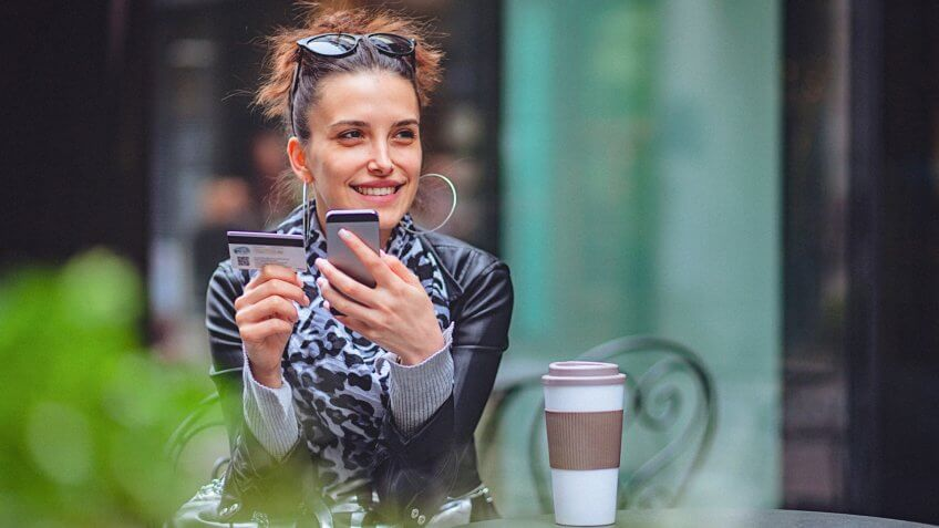 Close-up of a beautiful young woman in the city while using her credit card and a smartphone for an online transaction.