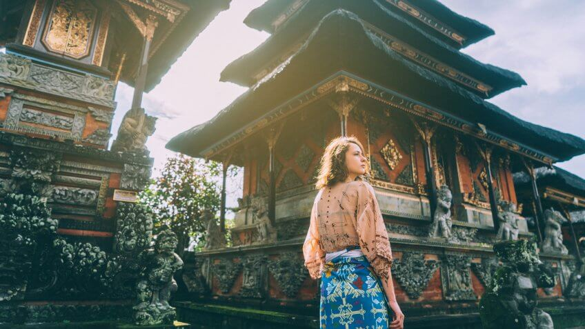 Young Caucasian woman walking in Balinese temple, Indonesia.