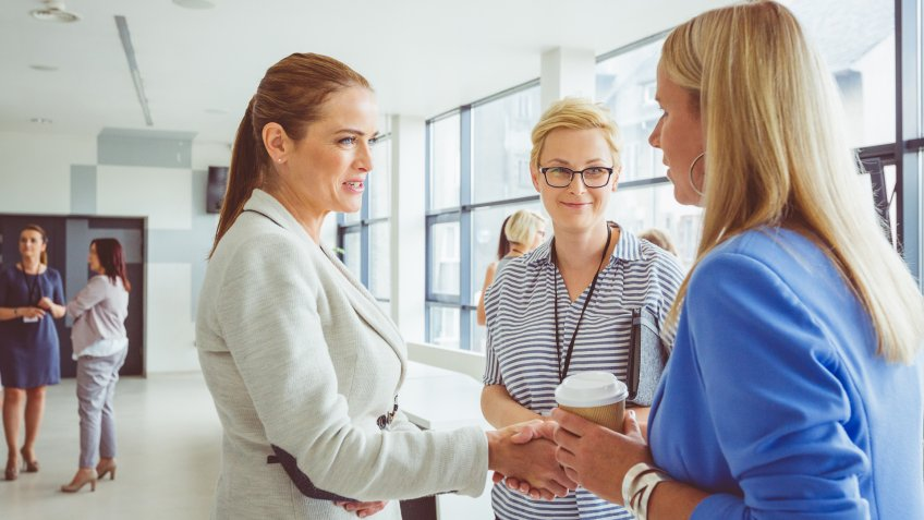 Mature woman shaking hand with young woman during seminar.
