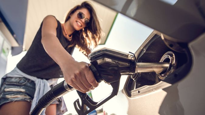 Close up of a beautiful woman refueling the gas tank at fuel pump.