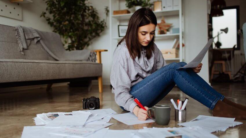 Young woman working on a project on the floor of her future office.