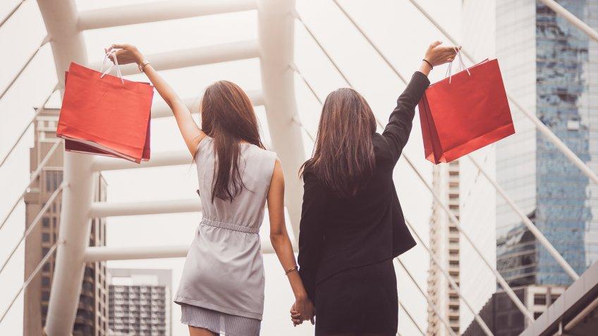Shopaholic lifestyle friendship women holding shopping bag in shopping mall center.