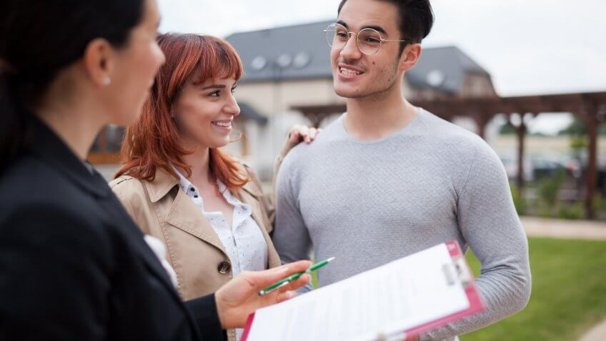 Real estate agent consulting young couple about buying new home.