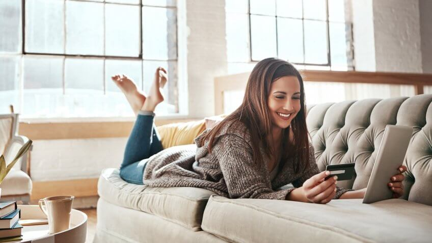 Shot of a young woman doing some online shopping while relaxing on her sofa.
