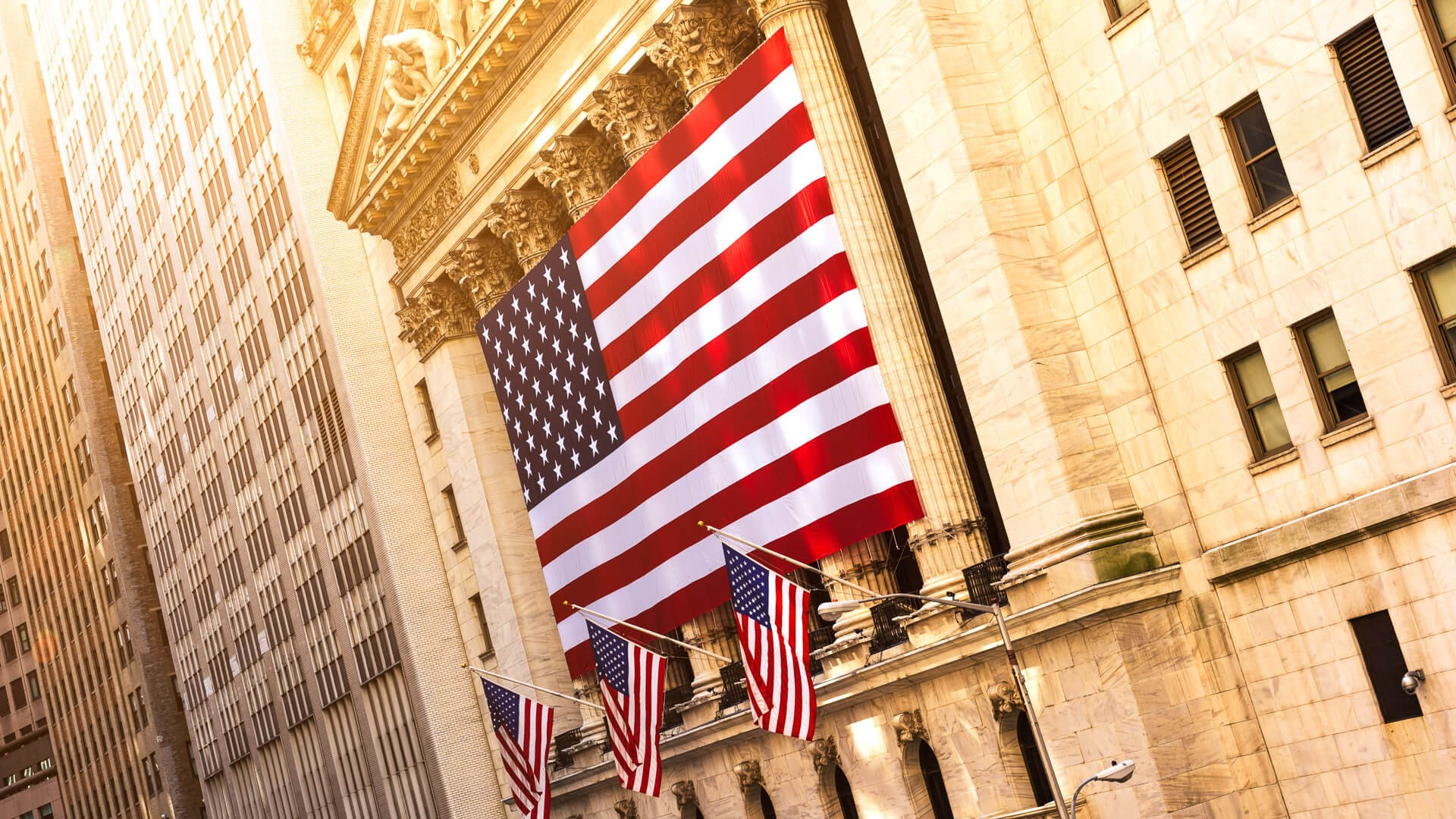 Famous Wall street and the building in New York, New York Stock Exchange with patriot flag.