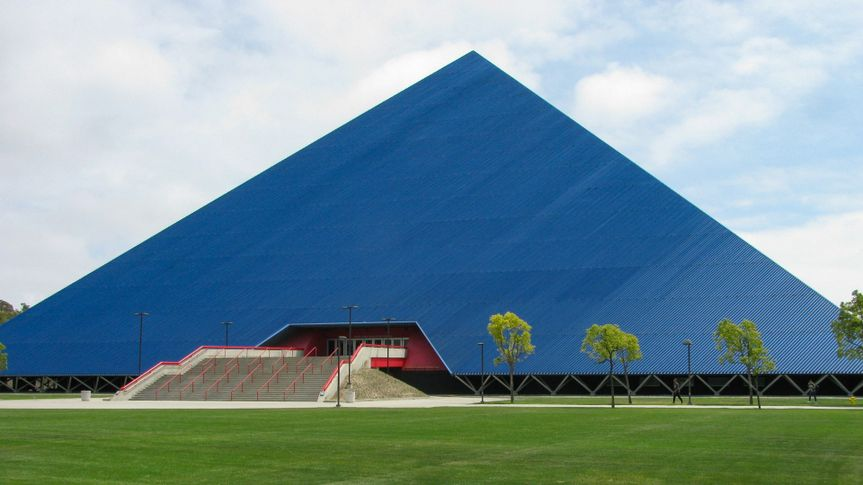 Long Beach, California USA - May 11, 2018: Walter Pyramid sports arena north face on the campus of the state University, set back from Atherton Street by a wide lawn of green grass.