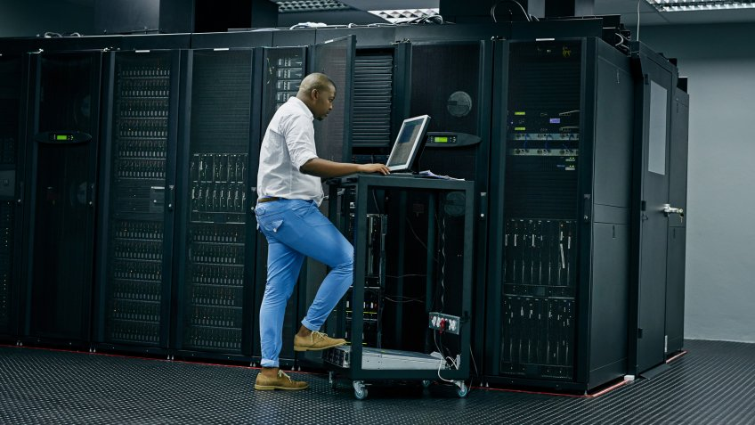 Shot of an IT technician using a computer while working in a data center.