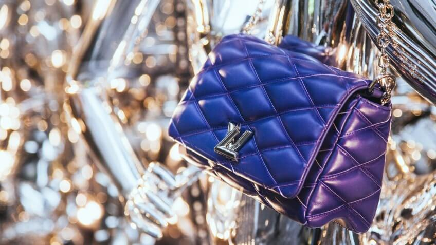 Milan, Italy - December 15, 2015: Louis Vuitton luxury leather bag in the shop window in Milan's fashion district Via Monte Napoleone showcasing the latest fashion news in an original way.