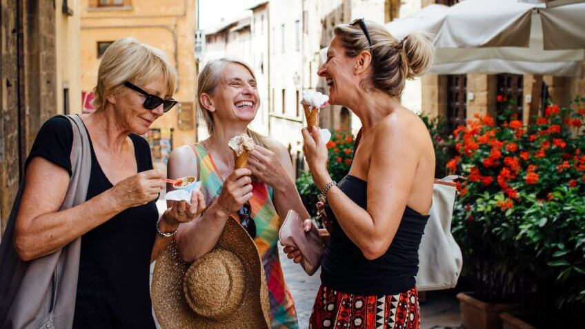Three mature female friends standing eating Italian ice-creams while in a street in Tuscany during summer.