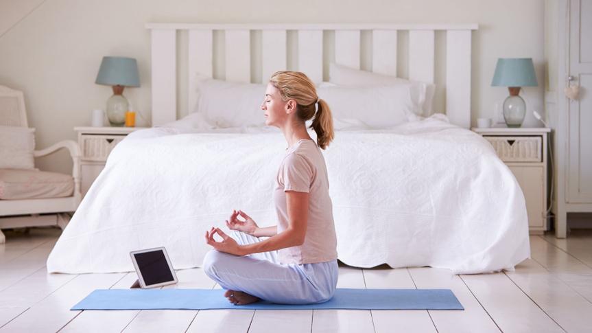 Woman With Digital Tablet Using Meditation App In Bedroom.