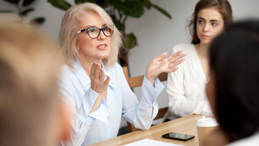 Attractive aged businesswoman, teacher or mentor coach speaking to young people, senior woman in glasses teaching audience at training seminar, female business leader speaker talking at meeting.
