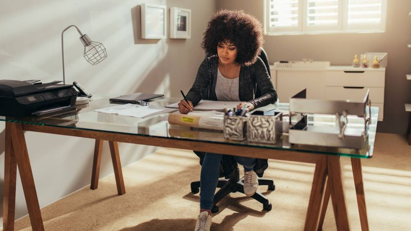 African woman working on new building plans while sitting at her desk.