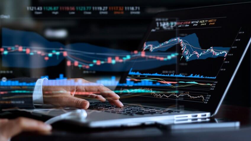 Businessman with statistic graph of stock market financial indices analysis on laptop screen, finance data and technology concept.
