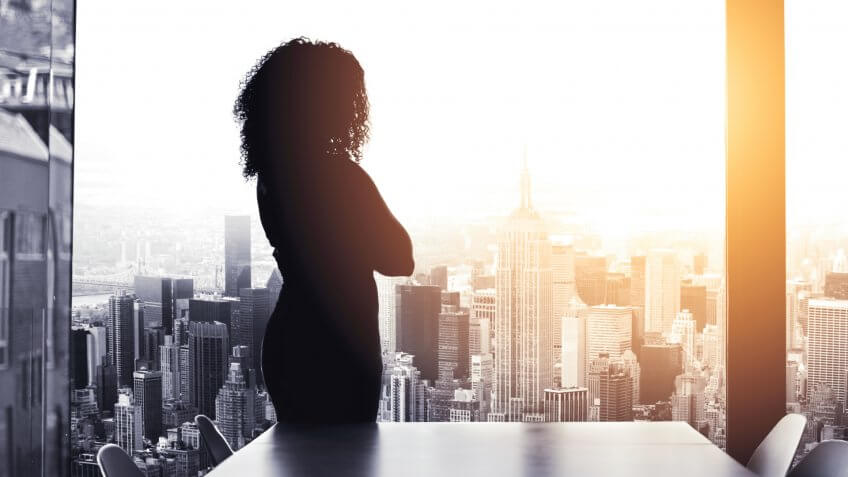 Silhouetted shot of a young businesswoman looking at a cityscape from an office window.