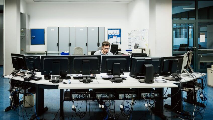 Engineer is working behind several work stations in a big control room.