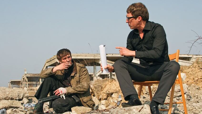 director talking with actor on set