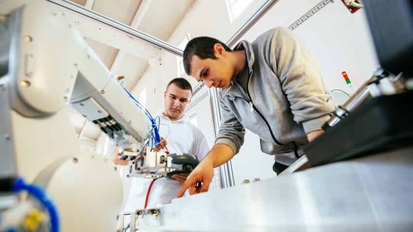 Engineers working on development of automated production line with robotic parts and applied software in order to increase productivity.