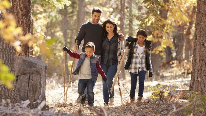 Happy Hispanic family with two children walking in a forest.