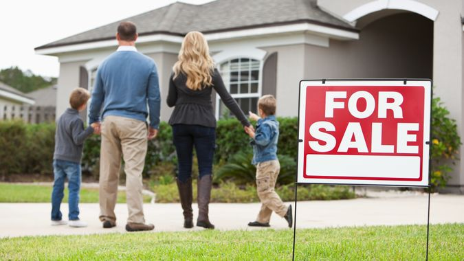 Family with two boys (4 and 6 years) standing in front of house with FOR SALE sign in front yard.