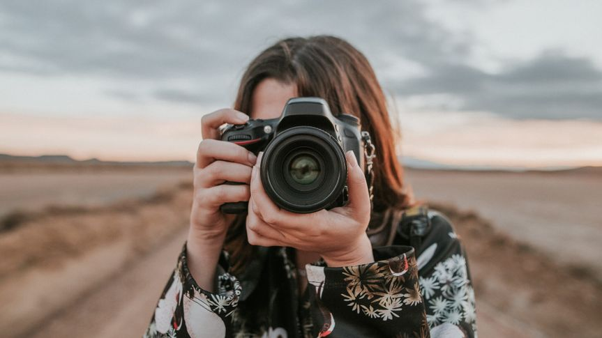 A young woman using a DSLR camera.