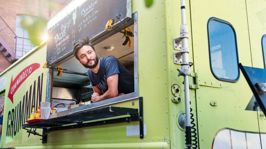 Adult man with beard waiting for clients in food truck in a city street on a bright summer day.
