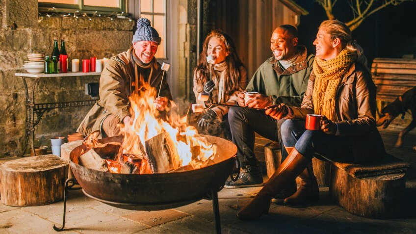Group of mature friends in their 30s and 40s gathered around a fire pit in a British garden.
