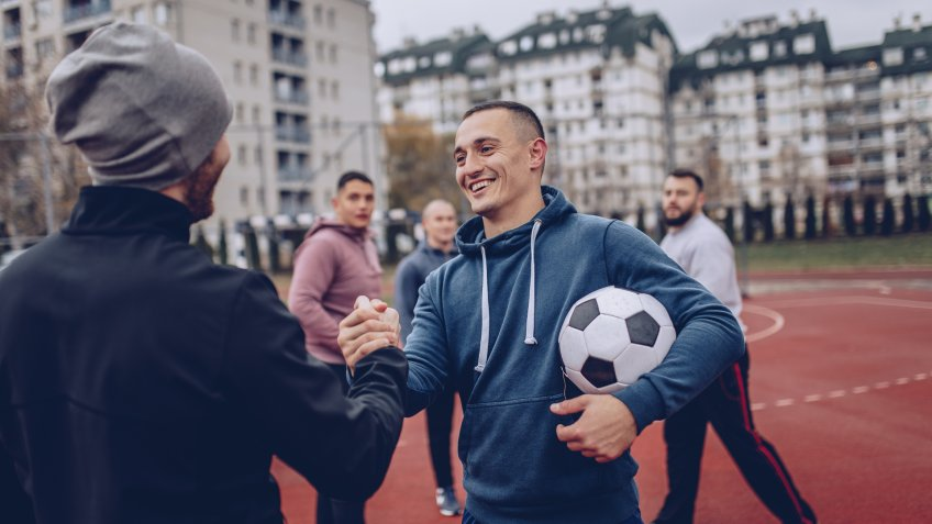 Group of men, playing soccer outdoors on the urban field, greeting before the game.