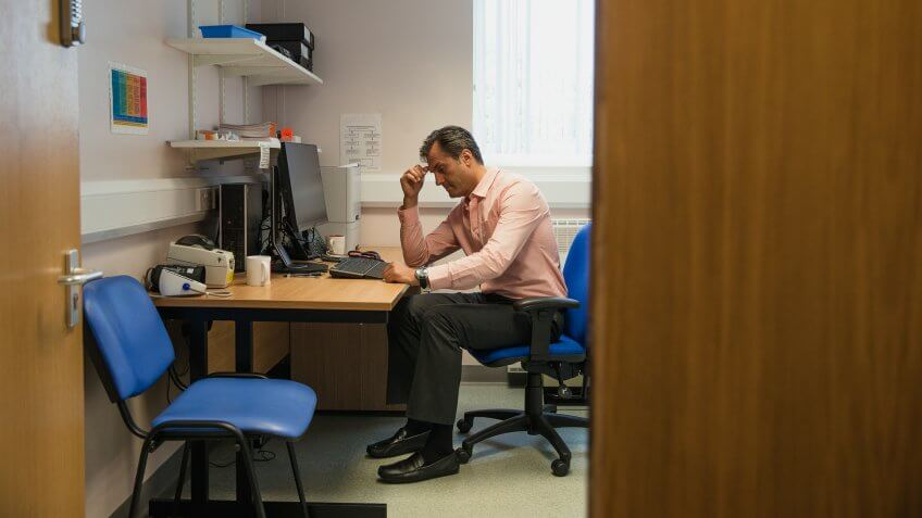 A doctor sits at his desk looking very worried.