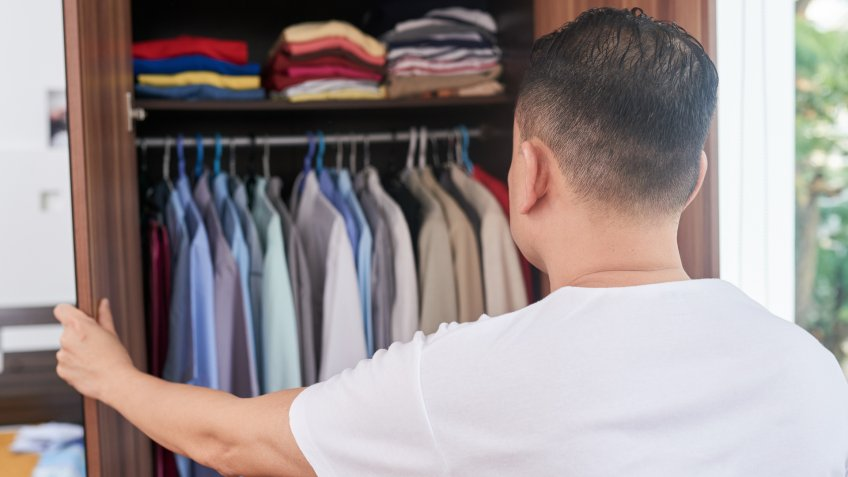 Rear view of young man opened his closet and choosing shirt for work in the office.