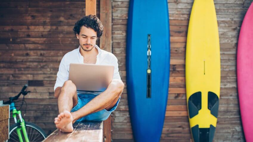 Young man using laptop outdoors in the summer with surfing boards in the background.