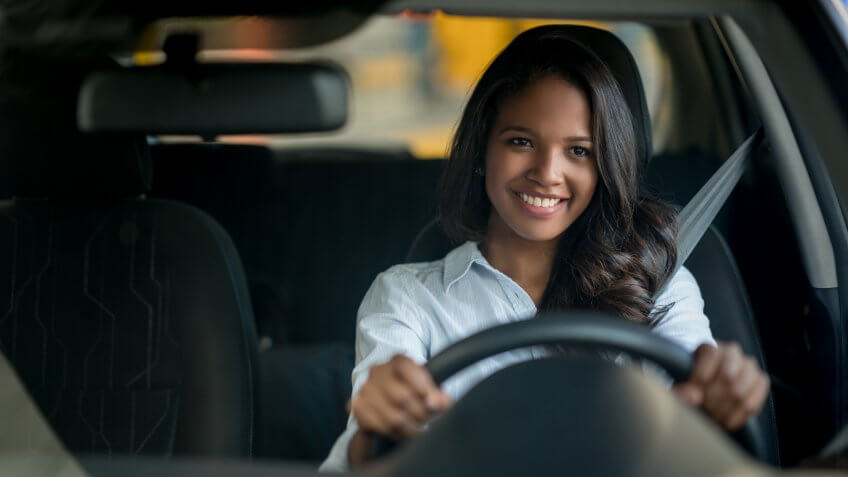 Happy African American woman driving a car at a dealersehip or an auto repair shop - lifestyle concepts.