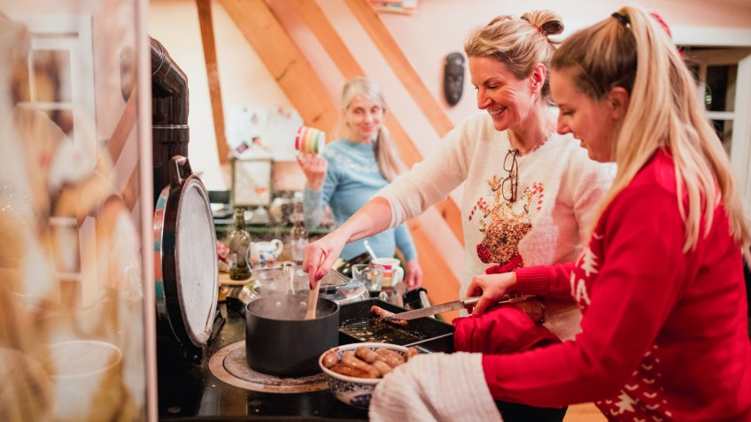 Three women are preparing christmas breakfast in the kitchen at home.