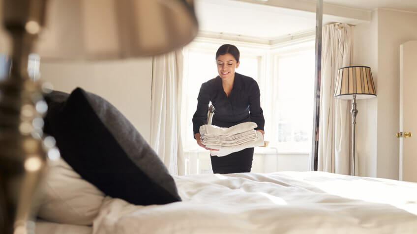 Chambermaid placing linen on hotel room bed, low angle view.